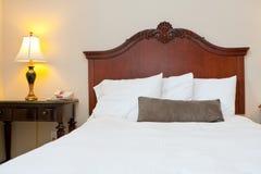 Comfy bedroom with dark wood Stock Image