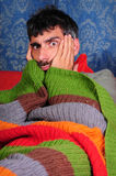 Comfy Couch Man's Comical Face. A funny photo of a man on the couch, wrapped in a blanket, holding his head with his hands Royalty Free Stock Photos