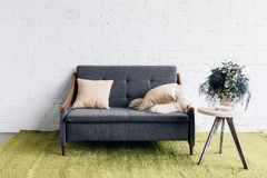 Comfy couch in modern living room with white brick wall and flower pot on table. Mockup concept Royalty Free Stock Photography