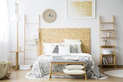 Comfy double bed. Standing in between two ladders in a monochromatic bedroom interior Royalty Free Stock Photography