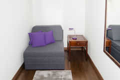 Comfy Gray Armchair with Purple Pillow near a Small Table Stock Photography