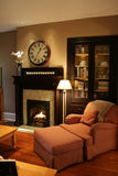 Comfy home fireplace. Comfortable room with easy chair, books and fireplace Stock Images