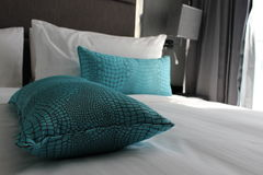Comfy hotel bed with cushions. Comfy hotel bed with turquoise cushions Stock Photography