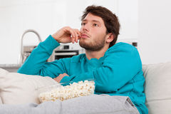 Comfy relax on a couch. A man relaxing on a couch with popcorn in comfy clothes Royalty Free Stock Images