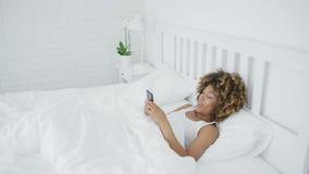 Χαλάρωση γυναικών χαμόγελου με το τηλέφωνο στο κρεβάτι απόθεμα βίντεο