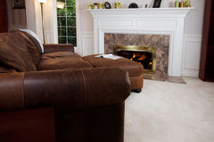 Comfy sofa by living room fire Royalty Free Stock Photography