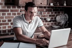Joyful entrepreneur typing while working at home. Comfy workspace. Waist p shot of a happy adult gentleman smiling while standing at a kitchen island and working Stock Images