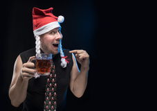 Comic actor man in cap with braids with a glass of beer, in anticipation of Christmas and New Year Stock Photo