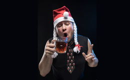 Comic actor man in cap with braids with a glass of beer, in anticipation of Christmas and New Year Stock Image