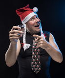 Comic actor man in cap with braids with a glass of vodka, in anticipation of Christmas and New Year. Comic actor man in cap with braids with a glass of vodka on Stock Images
