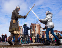 Comic `battle` with swords with the residents of the city as part of the entertainment program Shrovetide festivities Royalty Free Stock Photo