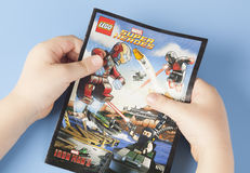 Comic book Lego Super Heroes in child's hands. Tambov, Russian Federation - January 12, 2015 Comic book Lego Marvel Super Heroes in child's hands. Blue royalty free stock photos