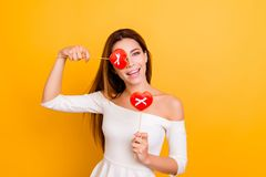 Comic, childish, charming, pretty girl  fall in love, holding, c. Losing her one eye with red cookies in heart shape, isolated over yellow background Stock Photos