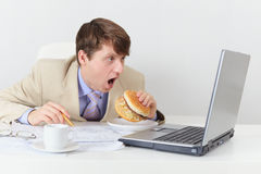Comic clerk eats sandwich looking at screen Royalty Free Stock Photos