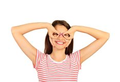 Comic crazy girl holding fingers near eyes like glasses and grimacing. emotional girl isolated on white background.  stock photos