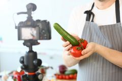 Comic Culinary Blogger Holding Organic Vegetables. Chef Recording Joke with Cucumber and Tomato for Blog on Camera. Man in Apron Showing Ingredient Assortment stock photo