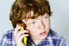 Comic freckled red-haired boy with mobile phone Royalty Free Stock Photo