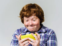 Comic freckled red-haired boy with mobile phone Royalty Free Stock Photos