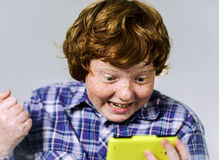 Comic freckled red-haired boy with mobile phone Stock Photo