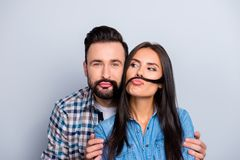 Comic, funky partners holding strand of hair with pout lips like. Mustache over grey background, fooling on valentine day royalty free stock photography