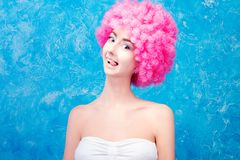 Comic girl with pink wig. Alone comic female / woman / girl with pink curved wig on blue background with cheeky emotion. Clown concept Stock Images