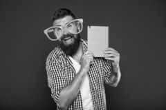 Comic and humor sense. Funny story. Study is fun. Funny book for relax. Book cover copy space. Hipster bearded man wear. Funny eyeglasses hold notepad or book royalty free stock photos