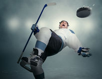 Comic moment of the Ice Hockey game: player dodging puck Stock Photography