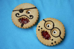 Comic pastries Professor and Pirate. Round pastries at form of comic smiles professor and pirate on a blue background Royalty Free Stock Images