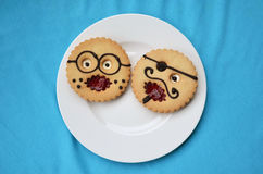 Comic pastries. Round pastries at form of comic smiles professor and pirate  on a white plate Stock Image