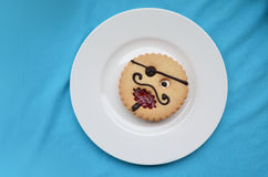 Comic pastry Pirate on the plate. Round pastry at form of comic smil  Pirate on a white plate Stock Photography
