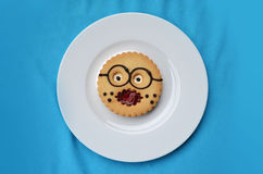 Comic pastry Professor on the plate. Round pastry at form of comic smil Professor on a white plate Royalty Free Stock Photos