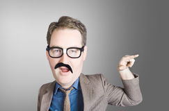 Comic portrait of a nerd businessman with big head. Pointing with surprise expression to grey copyspace. Nerds and geeks Stock Photo