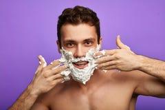 Comic positive man applying shaving foam royalty free stock photos