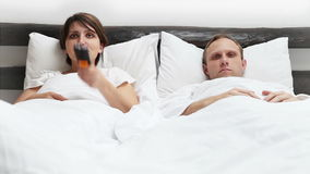 Comic scene - Wife and Husband  TV Remote control conflict in Bed stock footage