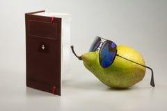 Comic still life reader. Green pear, sunglasses and a notebook - comic still life reader Stock Images