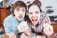Comical angry couple with flour on faces shouting. Comical angry young couple with flour on their faces holding dough and shouting Royalty Free Stock Photography