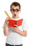 Comical boy in geek glasses. A comical boy student in geeky glasses writing in a book.  Please note eyeglasses are meant to distort eyes Stock Photo