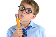 Comical boy holding a pencil and thinking. A child or schoolboy in a comical thinking pose Royalty Free Stock Photography