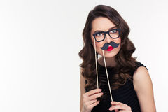 Comical curly young female playing with glasses and moustache booth. Portrait of comical curly young female with retro hairstyle playing with glasses and Stock Photos