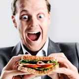 Comical man eating sandwich with funny expression stock images