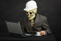 Comical man in helmet and skeleton mask. The comical construction superintendent in a helmet and a skeleton mask works with the computer Stock Photography