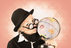 Comical nerdy person kissing the globe Stock Images