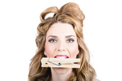 Comical pinup girl with big laundry peg in mouth. Comical cleaning girl holding large laundry peg in mouth. Eager pin up cleaner Royalty Free Stock Photography