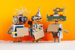 Comical robots with a cardboards mockups. Creative design robotic toys holding a blank empty paper posters, yellow wall. Background. copy space for text and royalty free stock photography
