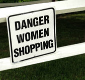 Comical sign. Danger women shopping comical sign on fence rail Stock Image