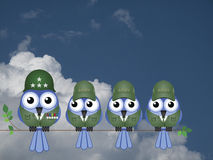 Comical Soldiers. Comical bird General and Soldiers sat on a tree branch against a cloudy blue sky Stock Image