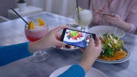 Comida útil, brazo de la mujer del blogger que usa el teléfono celular para la foto del vegetariano que come durante el almuerzo  almacen de video