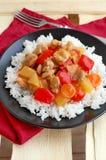 Comida agridulce con la carne del arroz, de la pimienta roja, de la piña, de la cebolla y del pollo en el paño rojo en la placa n Imagen de archivo libre de regalías