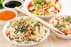 Comida asiática - tallarines con las verduras y los verdes, arroz frito Foto de archivo