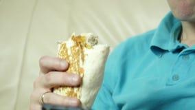 Comida basura antropófaga flaca con el gran disfrute el individuo come el bocado de los alimentos de preparación rápida Cámara le metrajes